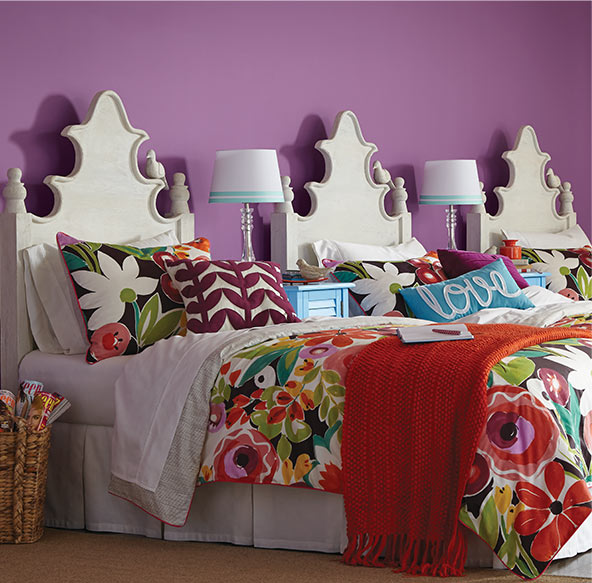 In a bedroom with a bold color on the walls, create visual interest by painting your headboard a bright white that stands out. Add some vibrant bedding to make it really pop.